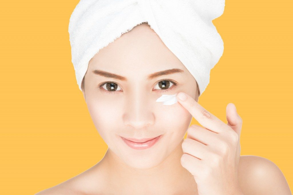 woman applying skin cream under eyes