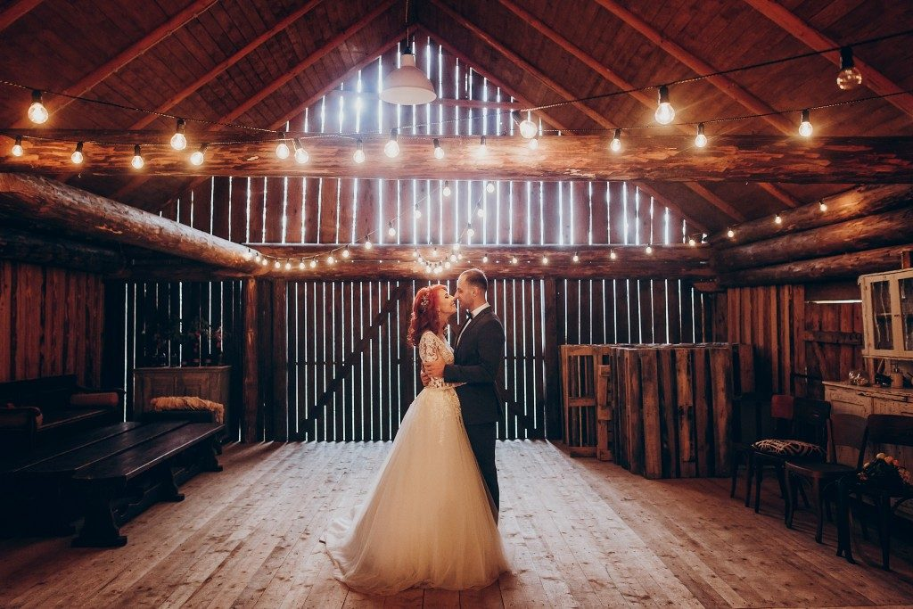 Groom and bride dancing in barn
