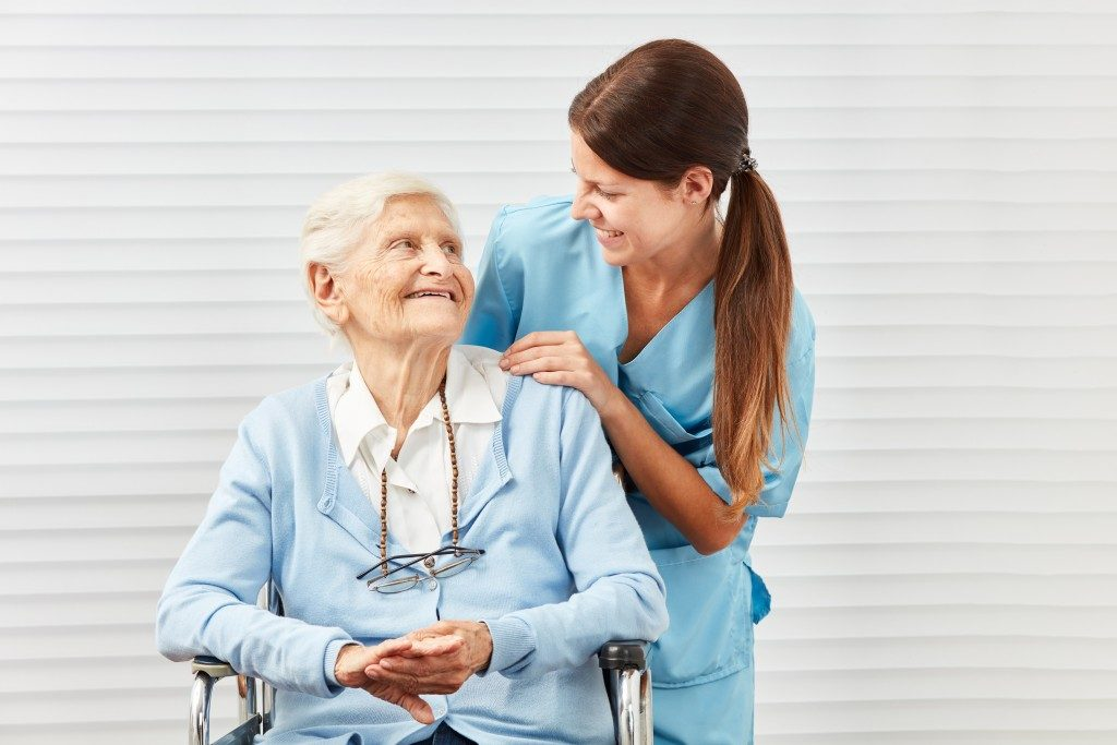 Senior woman and nurse smiling at each other