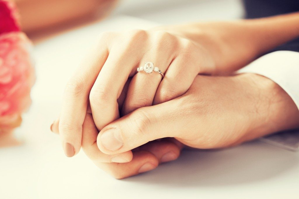 Female wearing engagement ring while hand being held by man