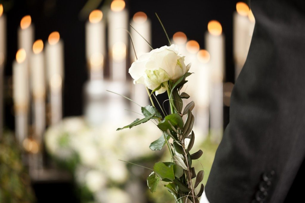 person holding a white rose in a funeral