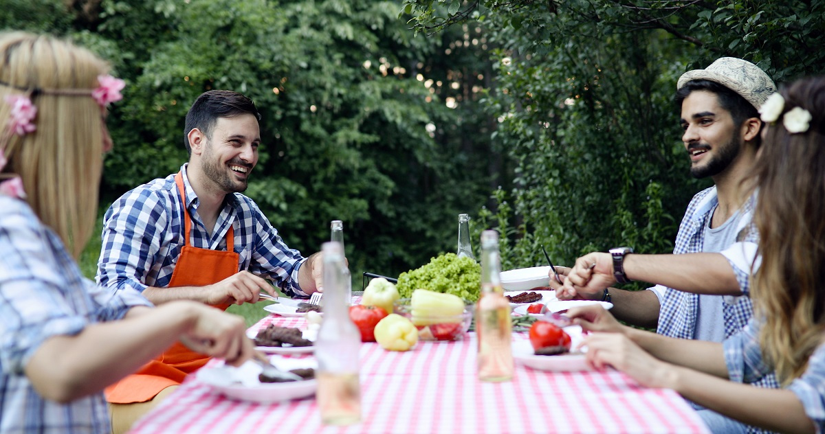 Group of happy people eating food outdoors