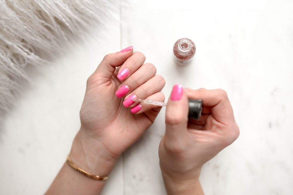 putting-on-pink-nail-polish