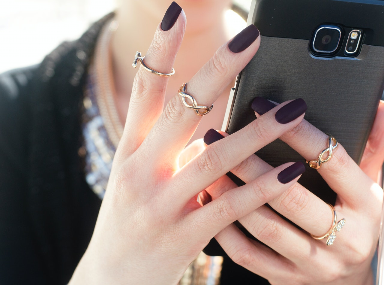 woman with nail polish holding smart phone