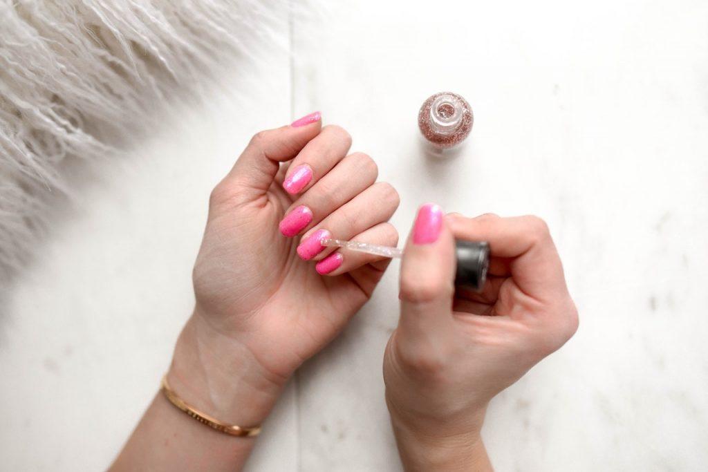 woman applying nail polish to her nails