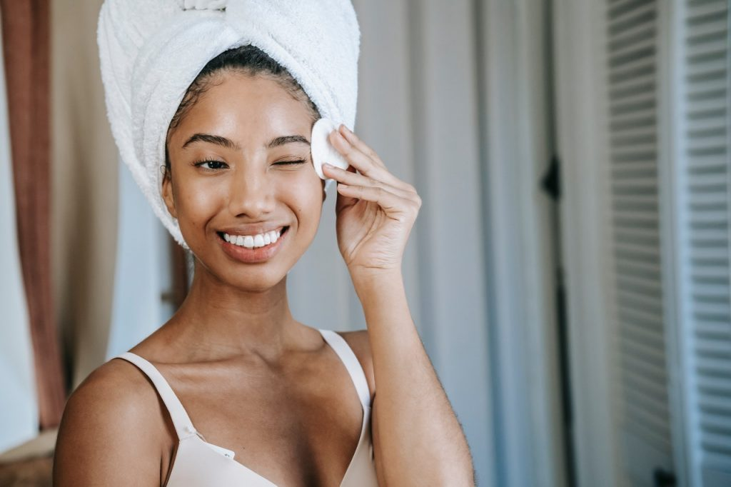 woman applying facial care product after showering