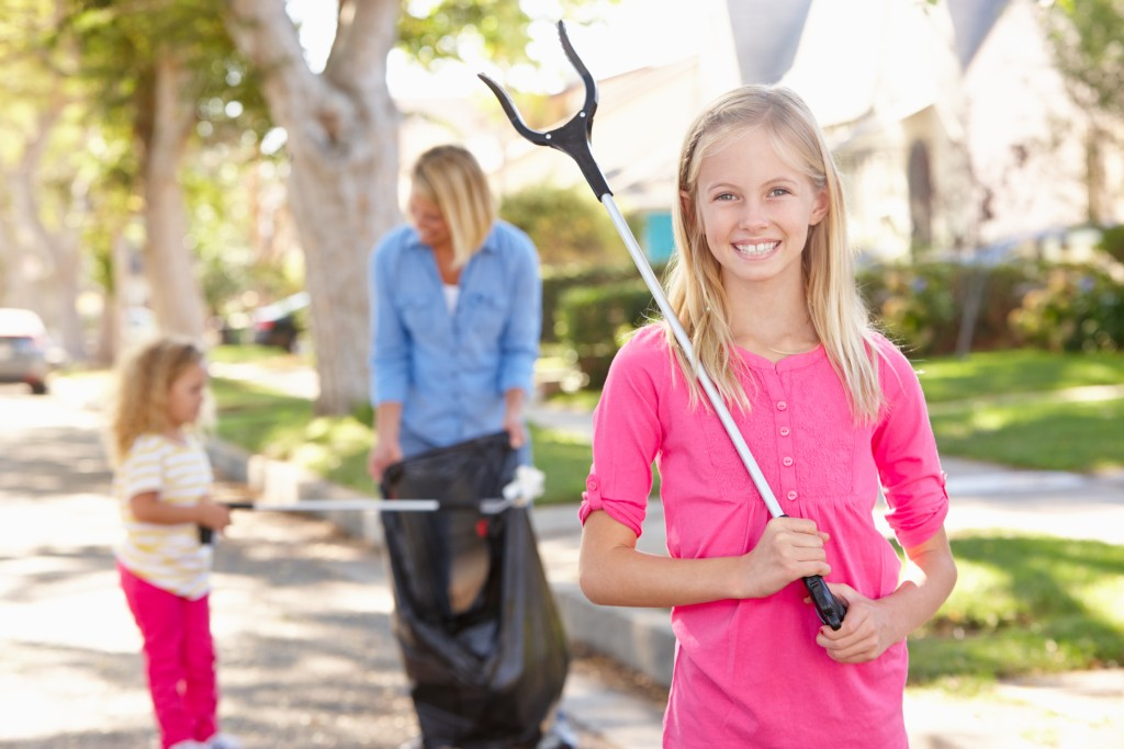 children and mother doing community clean up