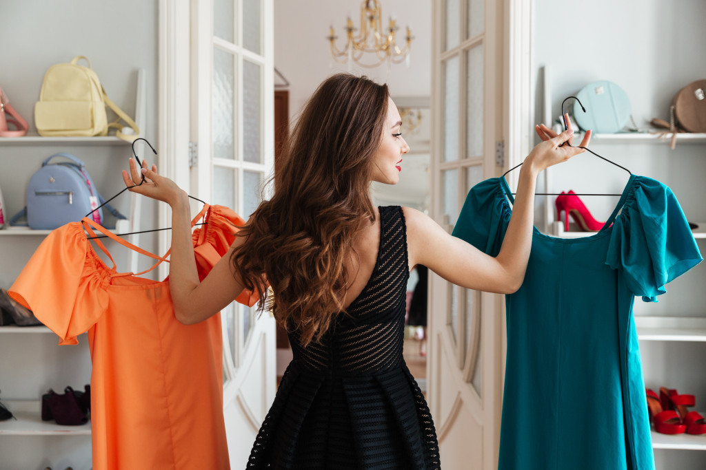 woman picking different colored dresses